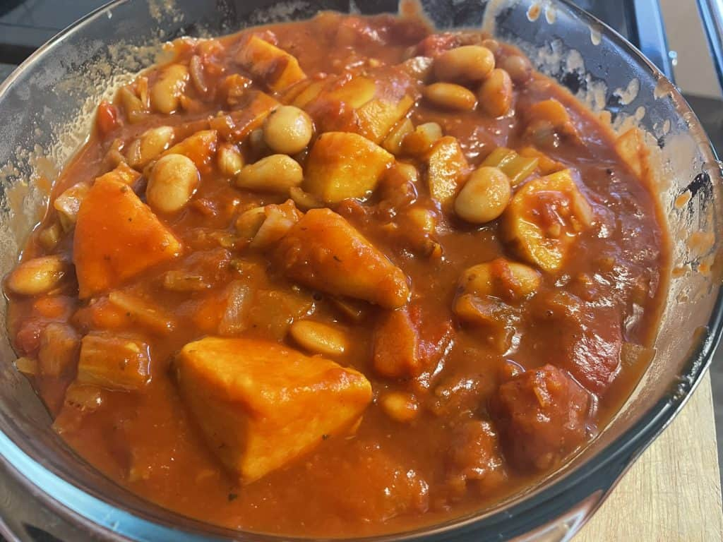 Vegan sausage casserole with sweet potatoes red pepper in a glass casserole dish