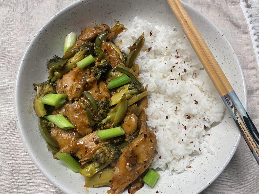 Mongolian beef and broccoli served in white bowl with chopsticks to side.