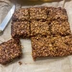 vegan traditional chocolate flapjacks with one cut off from main batch, knife to side, baking parchment underneath flapjack.