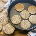 vegan oatcakes in cast iron skillet, with cooked oatcakes to side.