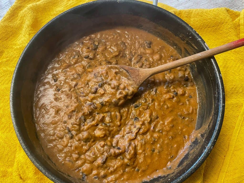 vegan refried beans in a skillet with wooden spoon and yellow teatowel.