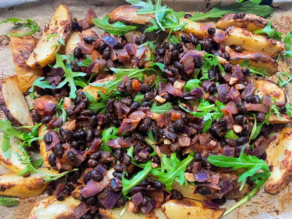 potato wedges with black bean mix added on baking tray.