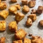 vegan crispy tofu bites sitting on greaseproof paper on baking tray.