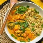 vegan Thai red curry sweet potato in white bowl with wooden spoon and wicket mat underneath.