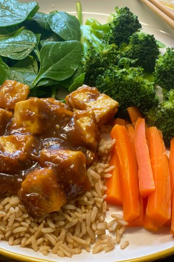 vegan sweet peanut sauce tofu in a with steamed broccoli