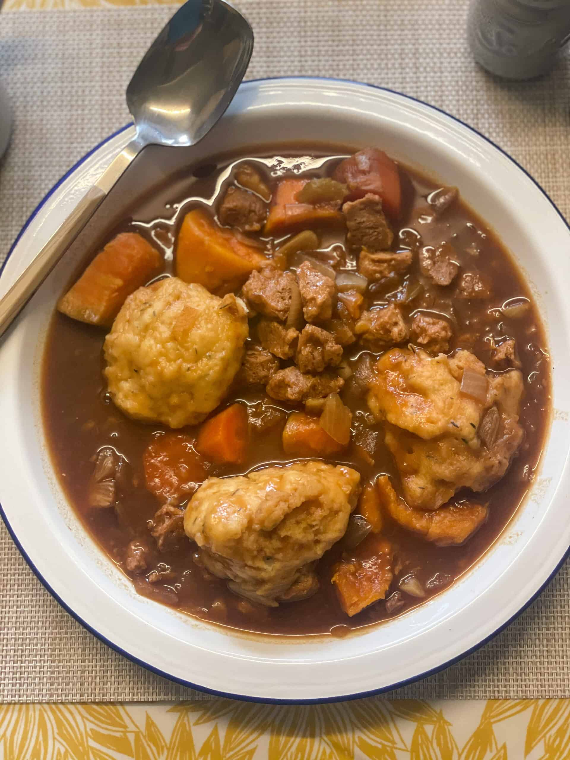slow cooker vegan beef stew and dumplings ready to eat in white bowl with blue rim, spoon at side of plate