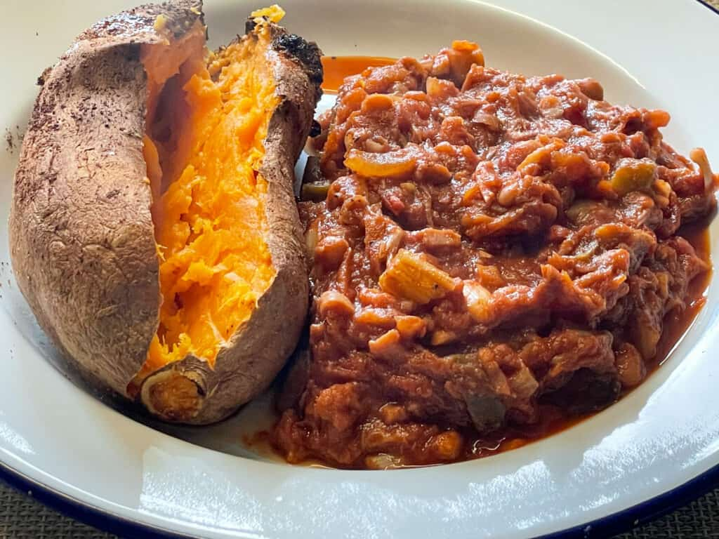 vegan campfire stew served in a deep rimmed white bowl with a sweet potato
