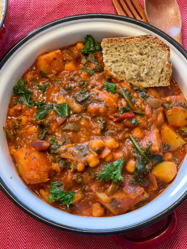 Spanish chickpea stew in a white bowl with red background