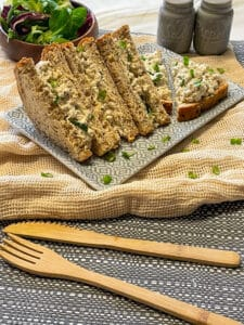 tofu egg and cress mayo sandwiches on a blue plate with fork and knife