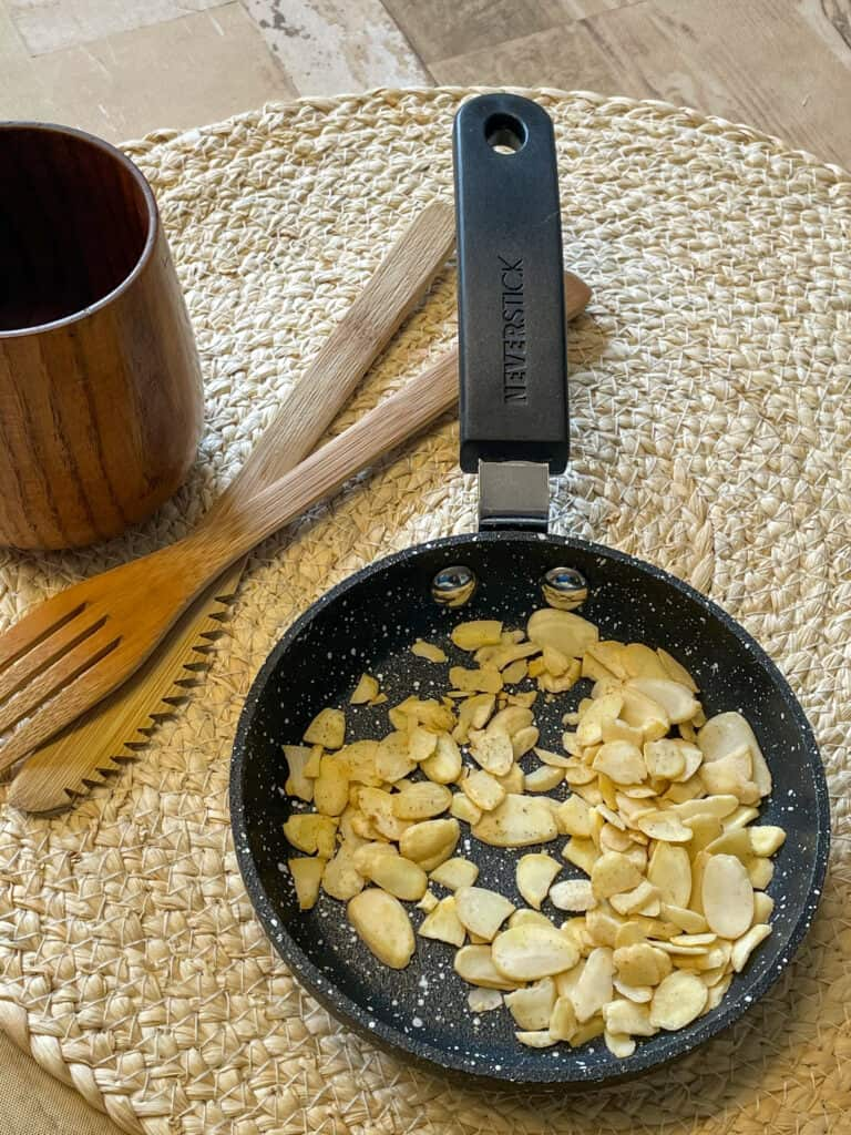 toasted almonds in a small pan on weaved mat, wooden fork and spoon, small wooden cup.