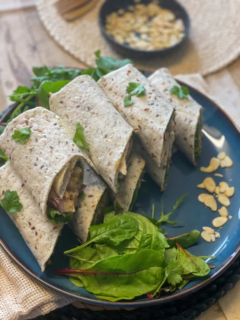 A stack of tortilla wraps filled with Coronation chickpea filling, sitting on blue plate with extra side salad and sprinkle of flaked almonds.