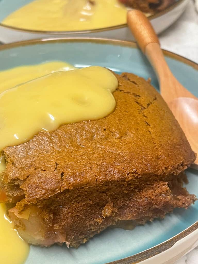 Pudding added to serving dish, with custard poured over, wooden eating spoon to side.