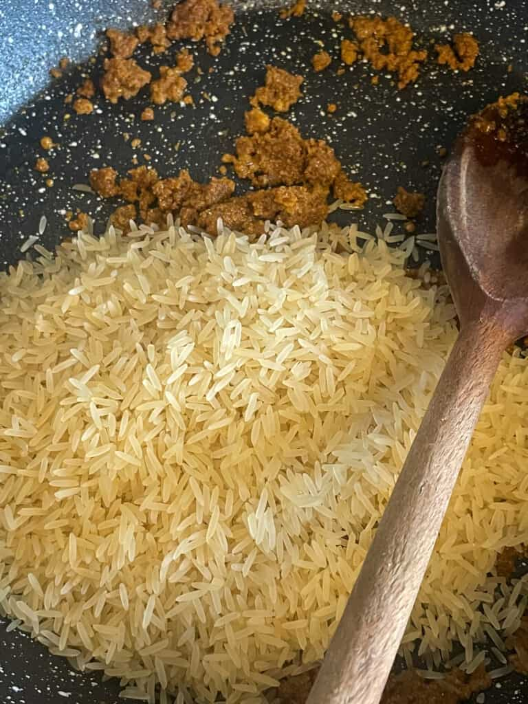 long grain rice with curry powder in a granite skillet pan