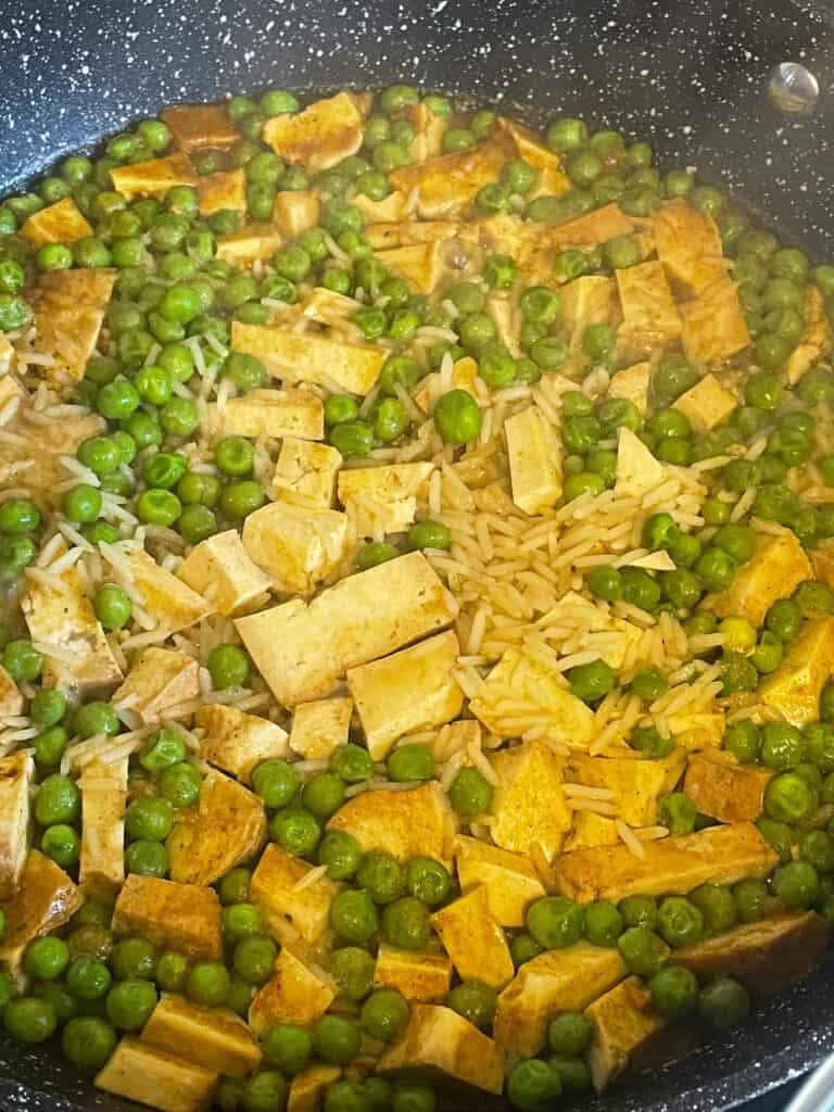 vegan kedgeree, peas and rice absorbing the veggie stock