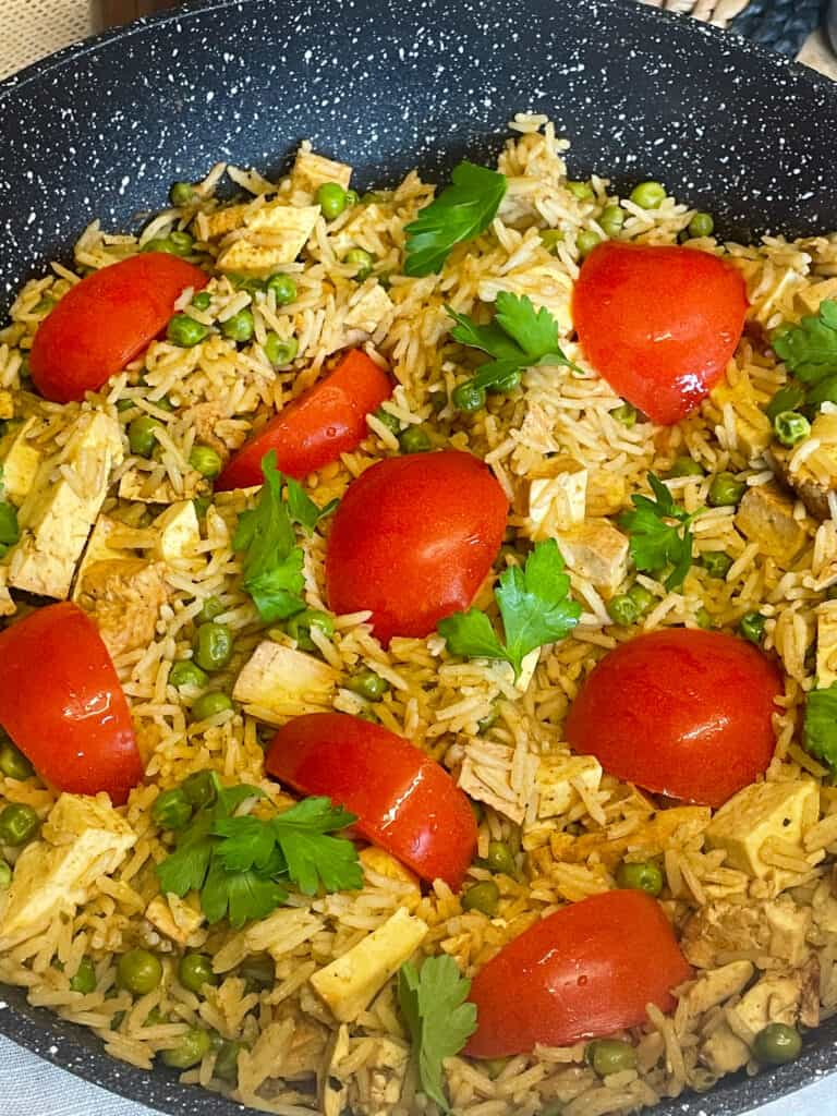 vegan kedgeree with red tomatoes and parsley in a shallow pan