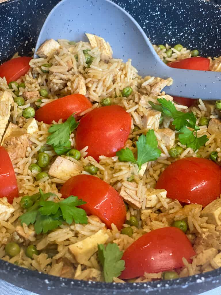 a close up of vegan kedgeree with a large grey serving spoon and black skillet