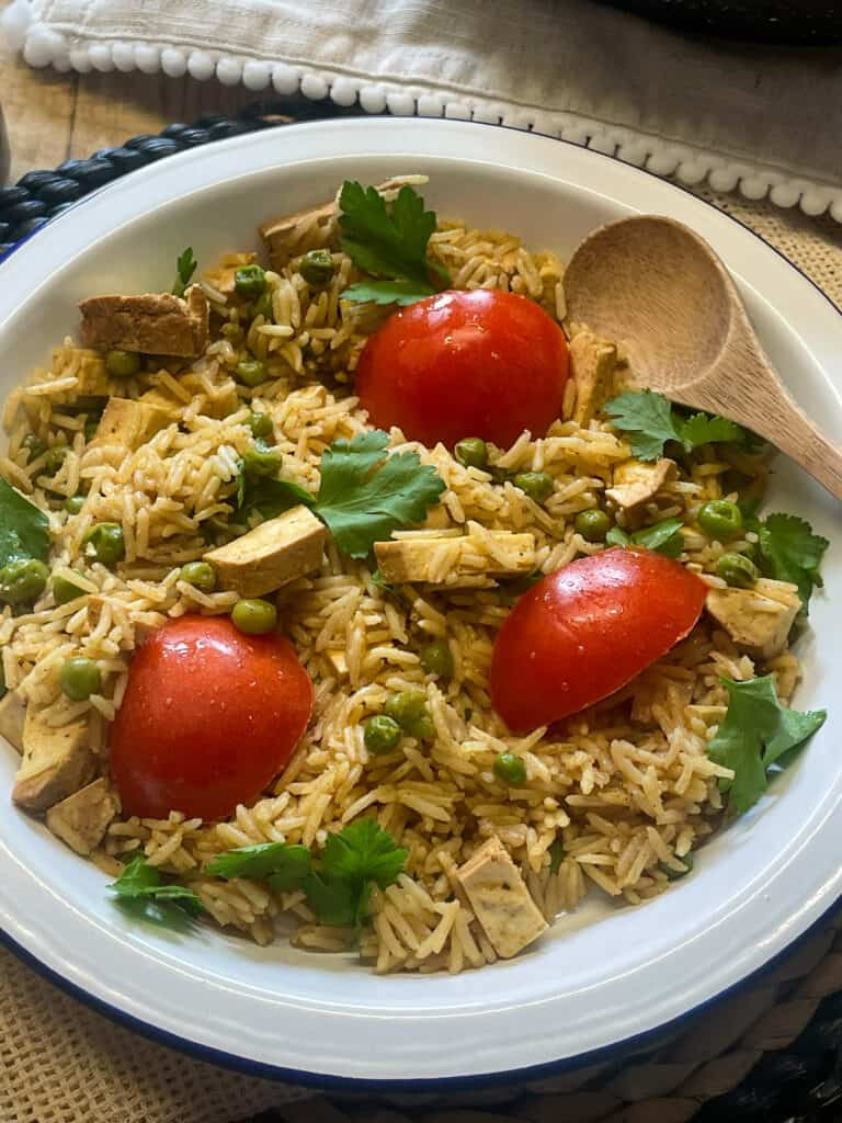 vegan smoked tofu kedgeree rice and tomatoes with corinader, in a bowl with small wooden soon