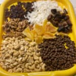 vegan trail mix ingredients set out on yellow tray.