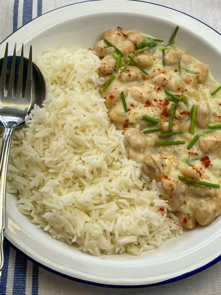 vegan butterbean 'chicken' supreme served with rice, spoon and fork at the side and blue striped tea towel