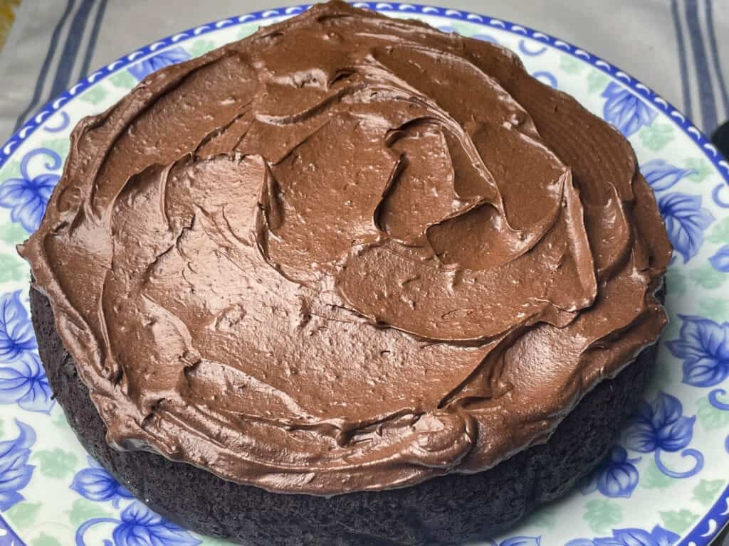 chocolate frosting spread on first cake
