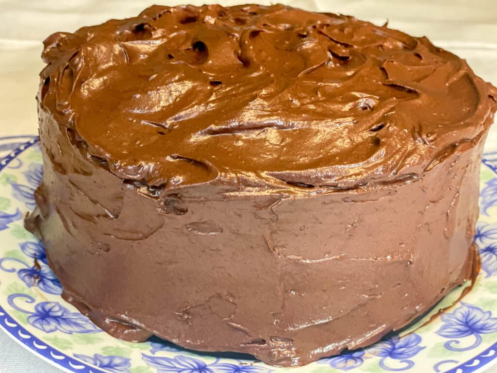 gluten-free chocolate cake completely covered with the chocolate frosting and sitting on a decorative blue flower plate