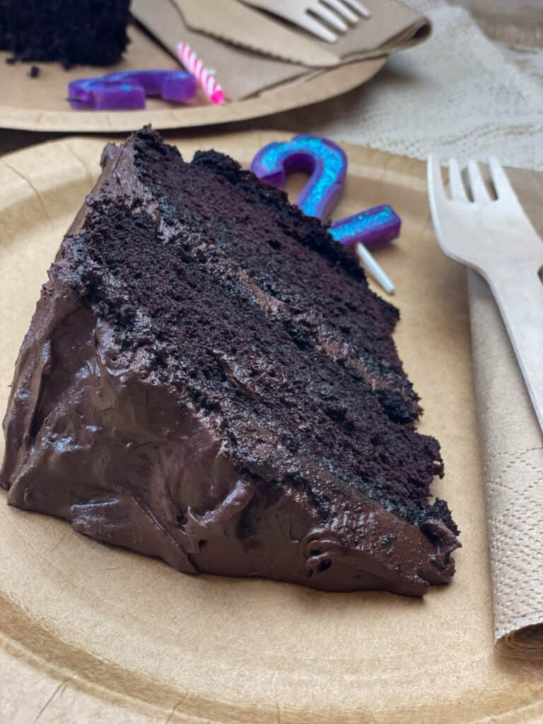 slice of vegan gluten-free chocolate cake on brown disposable plate with birthday candles, fork and napkin