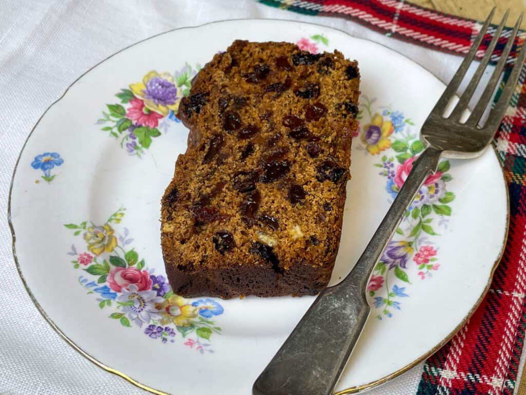 vegan fruit loaf cake on flowered cake plate with fork and on top of tartan napkin