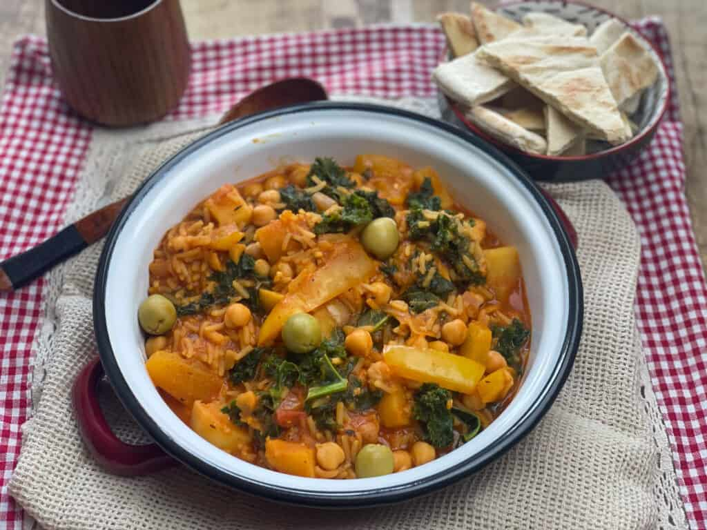 chickpea stew served with wooden cup with water and toasted pitta breads, sliced.