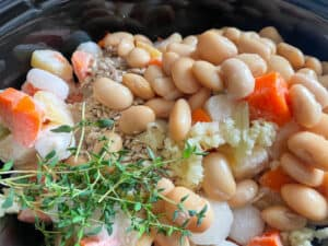 root veggies, garlic, butterbeans and fresh herbs in the saucepan