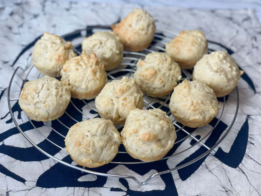 vegan quick dinner rolls cooling on circular wire rack with a cream cloth underneath that has a motive of a black lizard