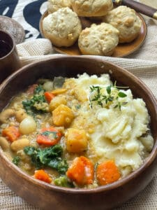 vegan medieval potage stew served in wooden bowl with quick dinner rolls on wooden plate and wooden cup to side