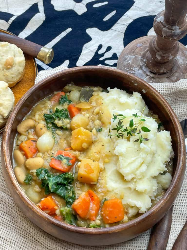 Medieval potage stew served in a wooden bowl, with fork and spoon, little bread rolls at the side, and candlestick