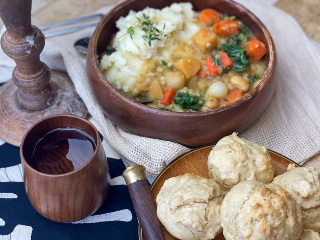 potage stew in a brown bowl with little bread rolls on a plate, with a brown handled knife at the side, small brown wooden cup with water and a wooden candle stick with wax drips.