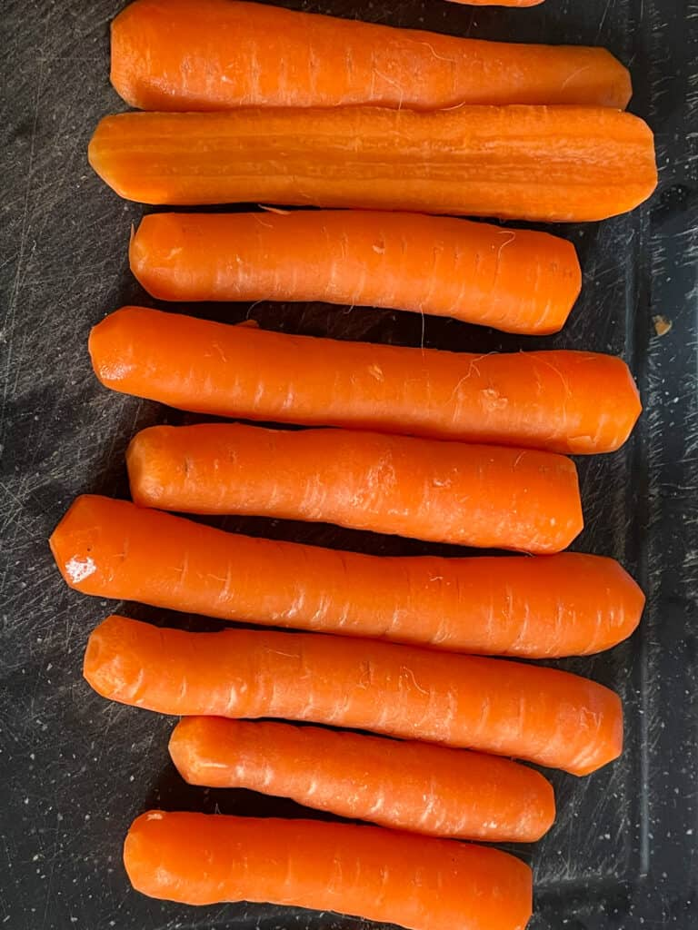 a line of carrots, peeled, topped and tailed.