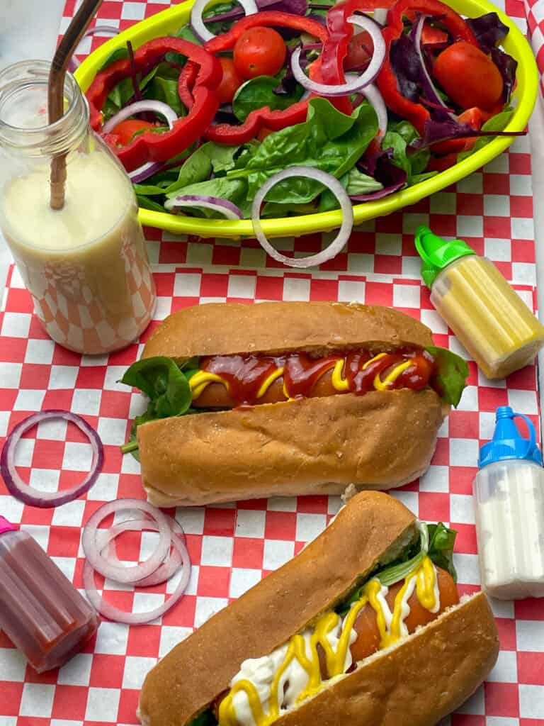 carrot hotdogs with milkshake, salad basket and sauce bottles, with red check mat underneath