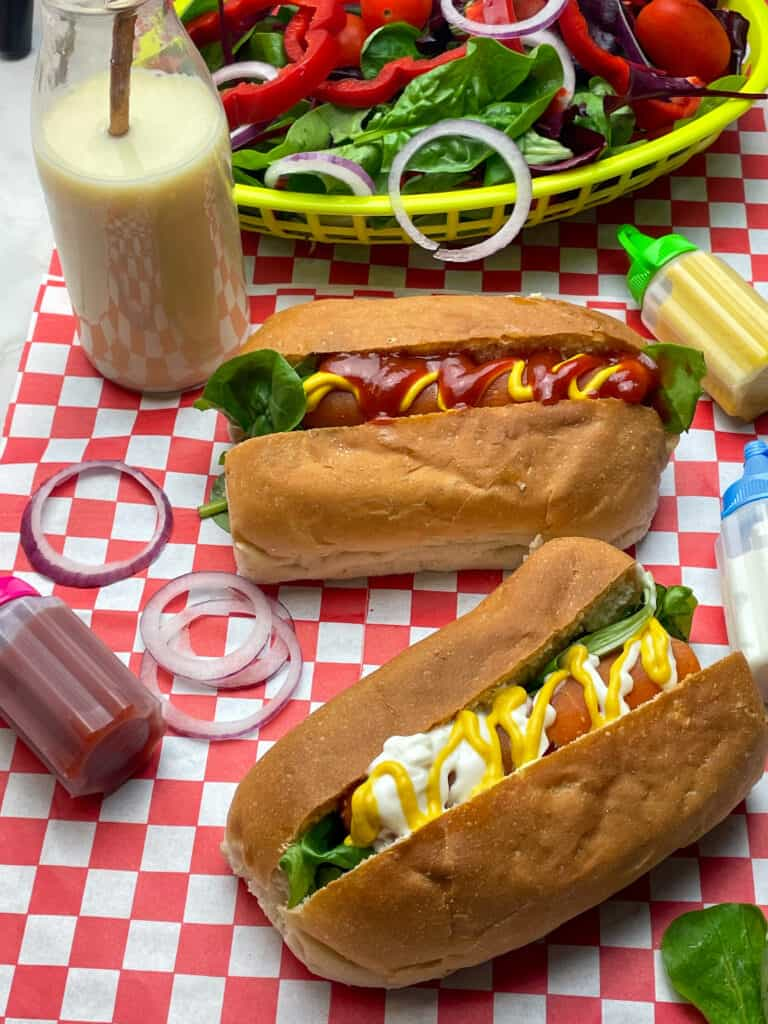 carrot hotdogs, with small glass bottle with milkshake and straw, small sauce bottles and a basket of mixed salad, on top of a red check mat