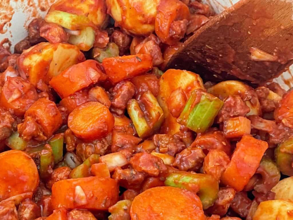 tomato puree and passata added to saucepan with beef stew veggies
