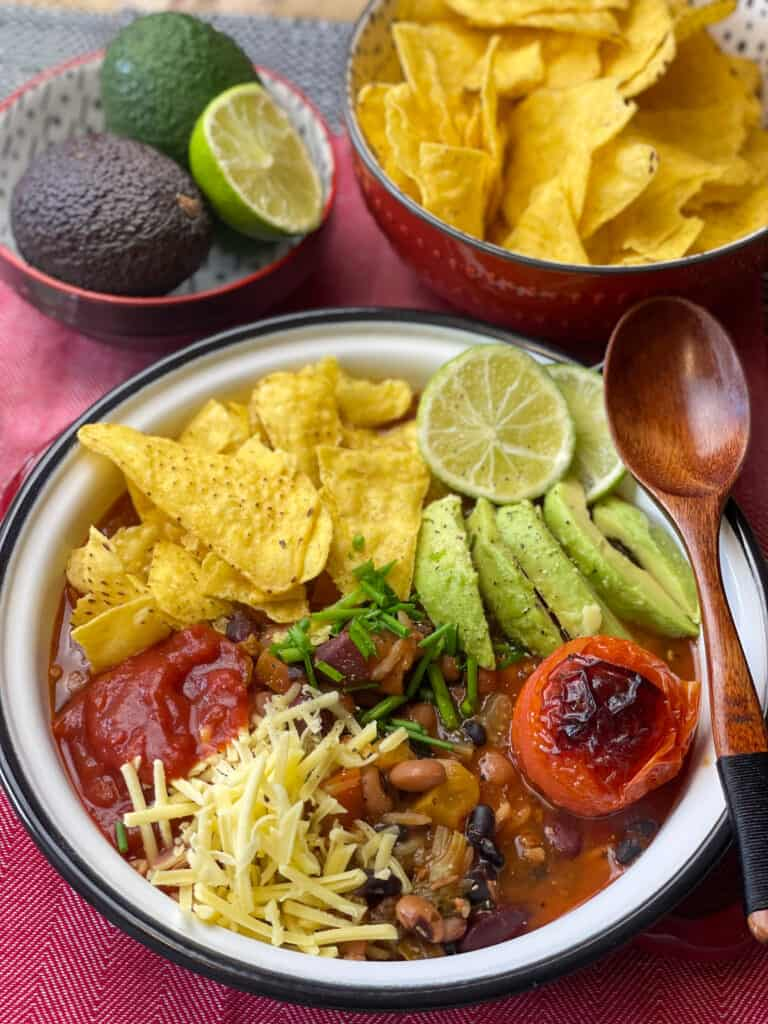 vegan taco soup served in white bowl with wooden spoon, tortilla chips in red bowl at side and a small bowl of 2 avocados and a lime slice.