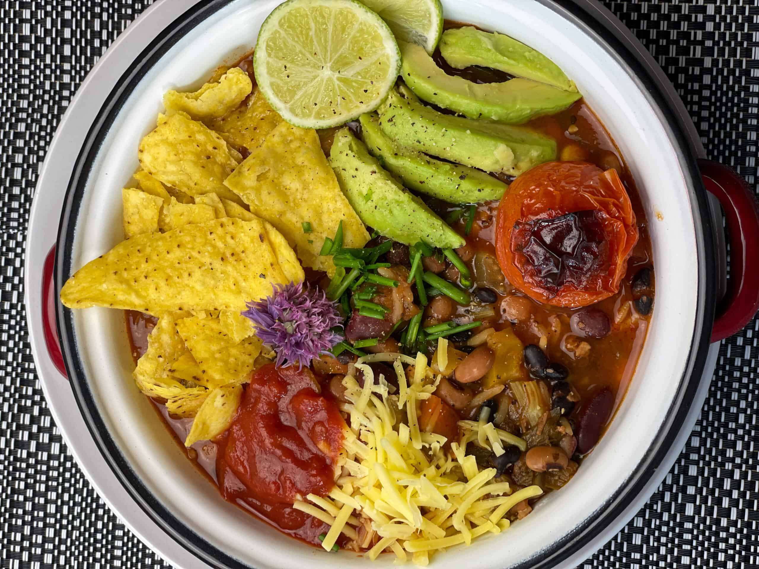 taco bean soup served in white bowl with black and white background.