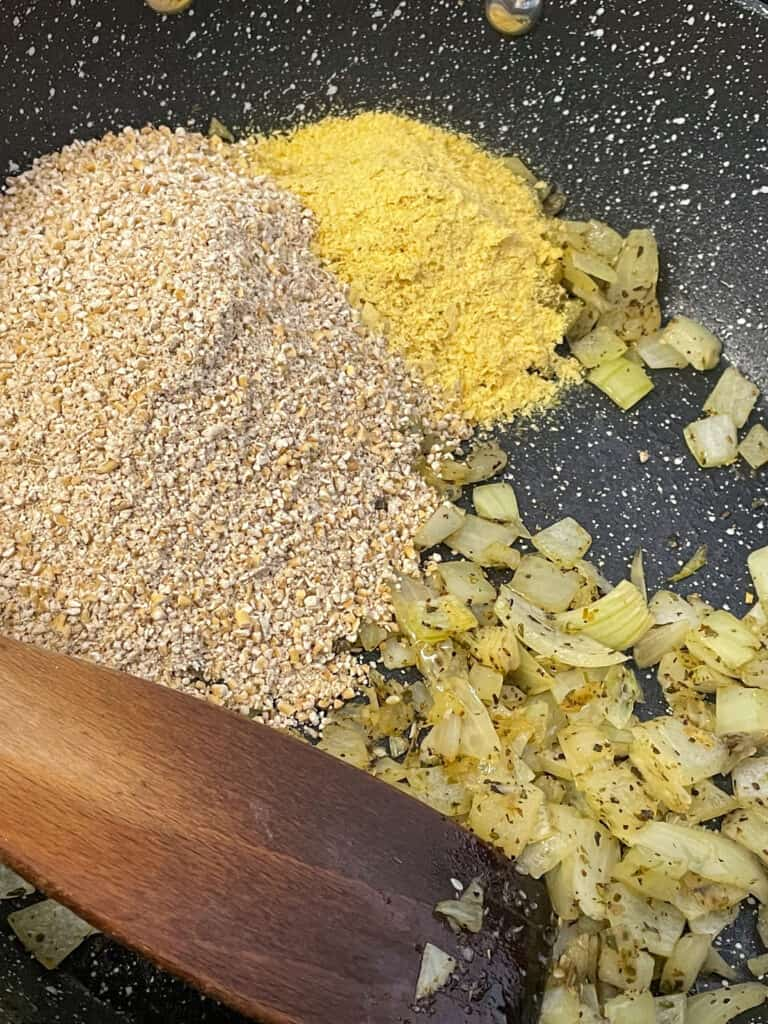 Oatmeal, and nutritional yeast added to pan with oatmeal and onions.