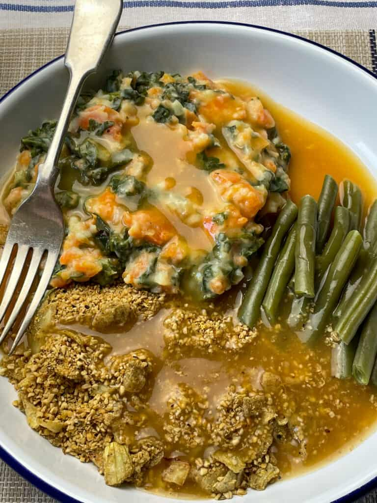 Skirlie served with gravy, green beans and veggie mash, fork to the side.