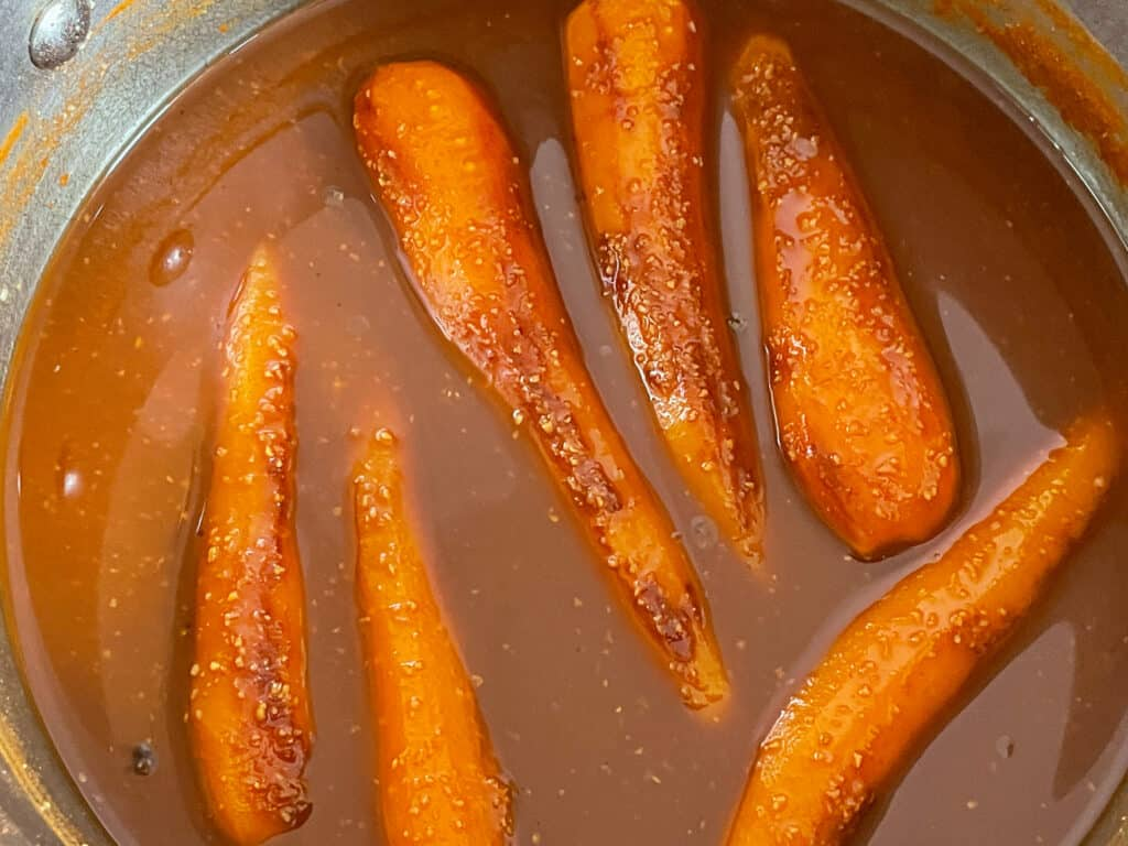 Carrot dogs cooking in liquid in a saucepan.