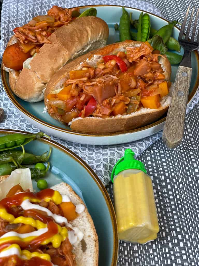 carrot hotdogs in rolls with campfire stew topping, mustard bottle to side, blue background.