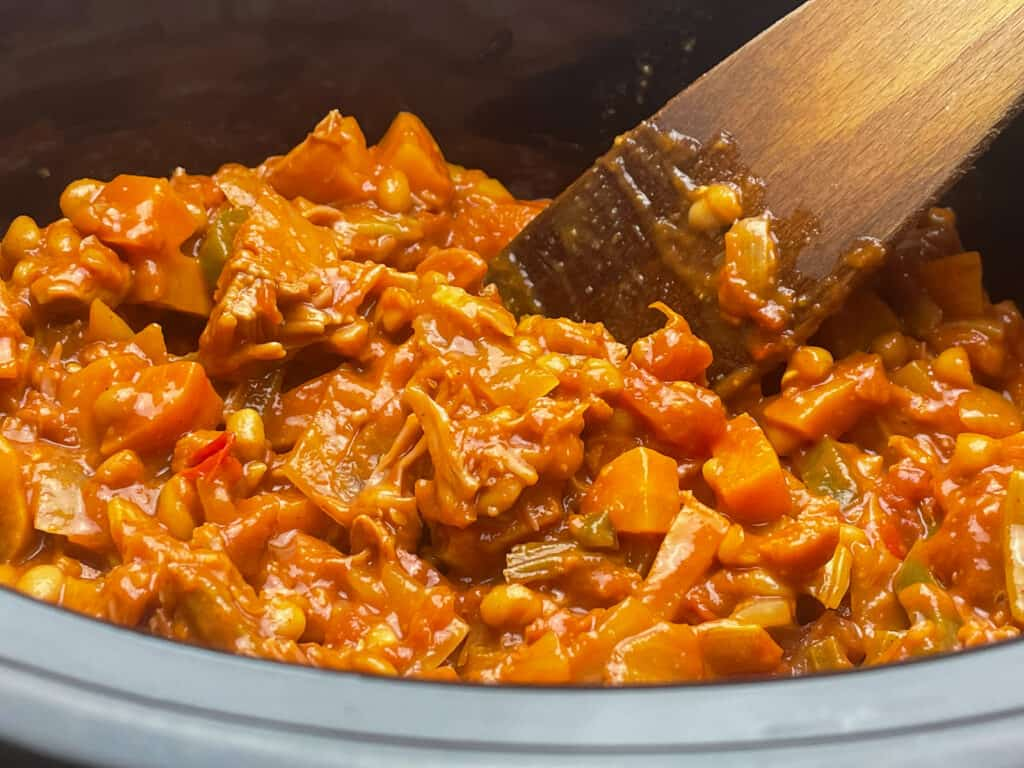 camp fire stew in the slow cooker with a mixing spoon.