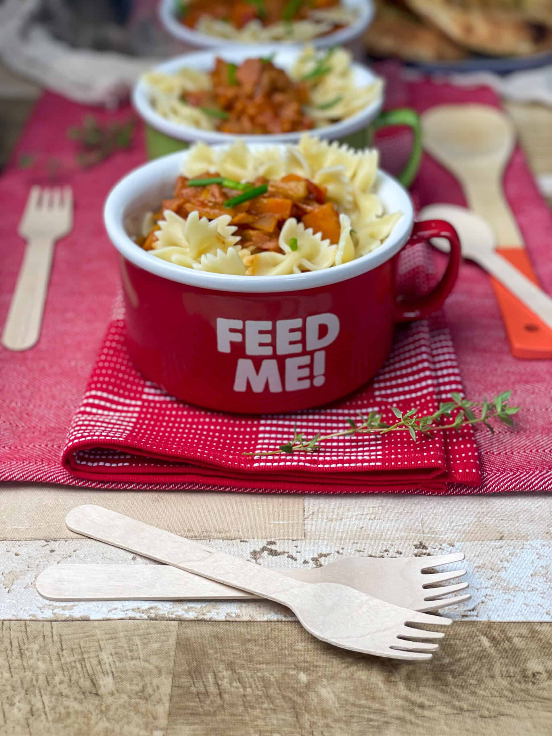 large red mug with 'feed me' text, forks to side, garlic bread in distance, red background.