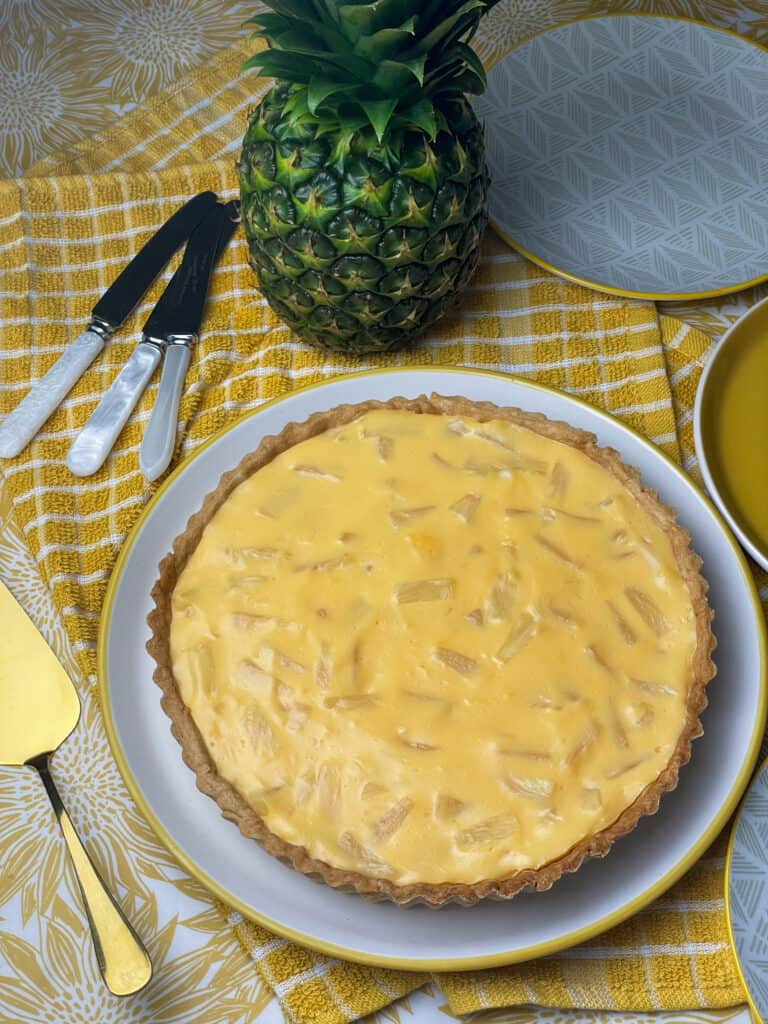 Vegan pineapple tart on serving plate, with dessert knifes off to side, serving plates at side, serving spatula to side and a green fresh pineapple at top.
