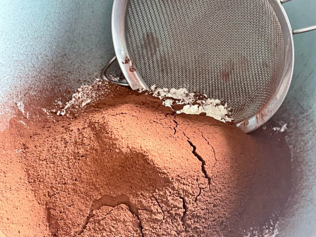 cocoa powder, flour and sugar in a green bowl with a sieve.