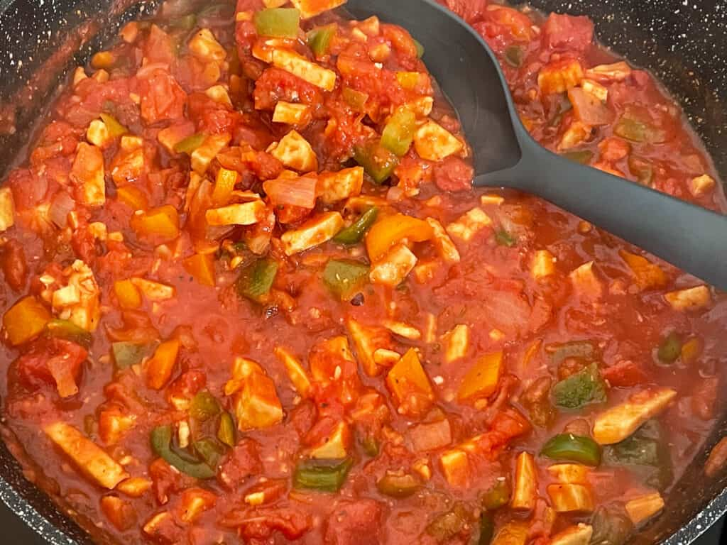 Bolognese sauce cooking in skillet with black ladle.