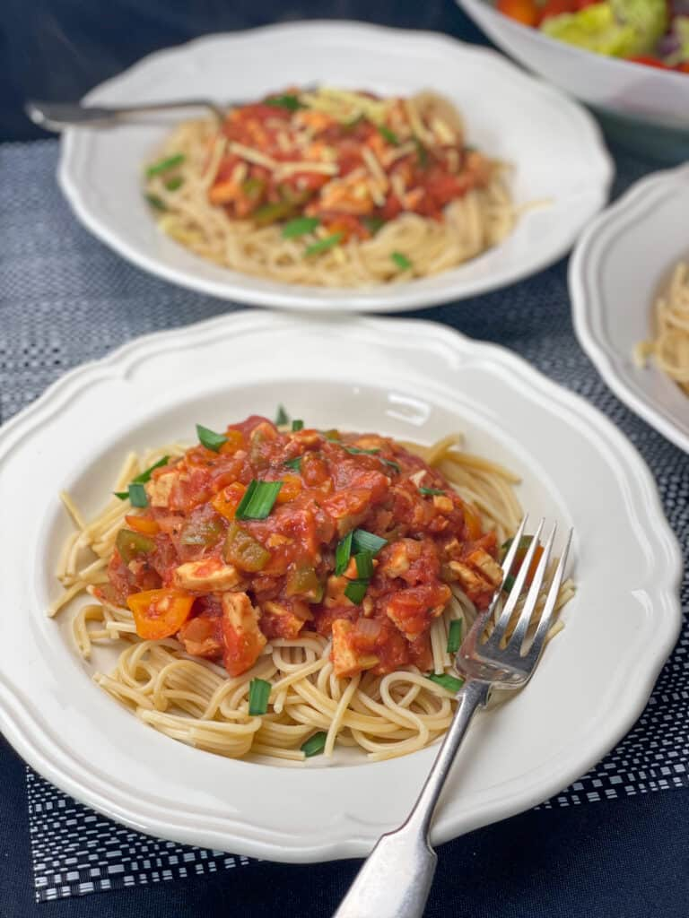 spaghetti Bolognese served in two white bowls with silver forks.