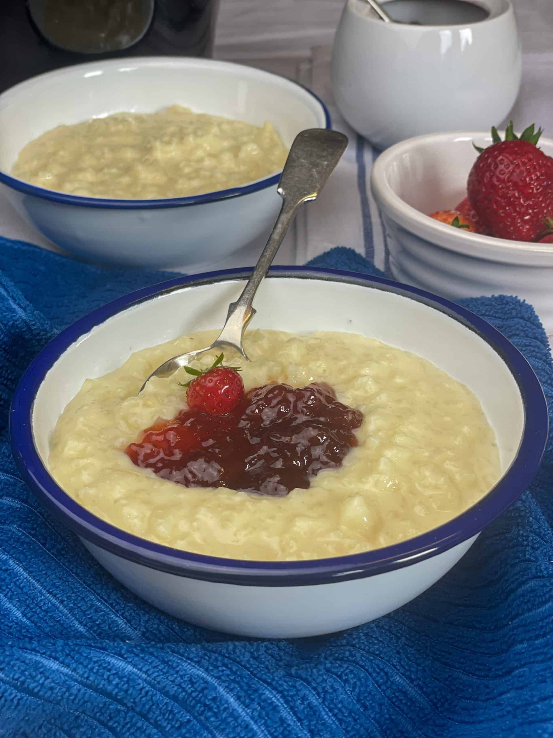 vegan slow cooker rice pudding served in enamel white bowls with small bowl of strawberries, and pot of jam in distance, blue background.